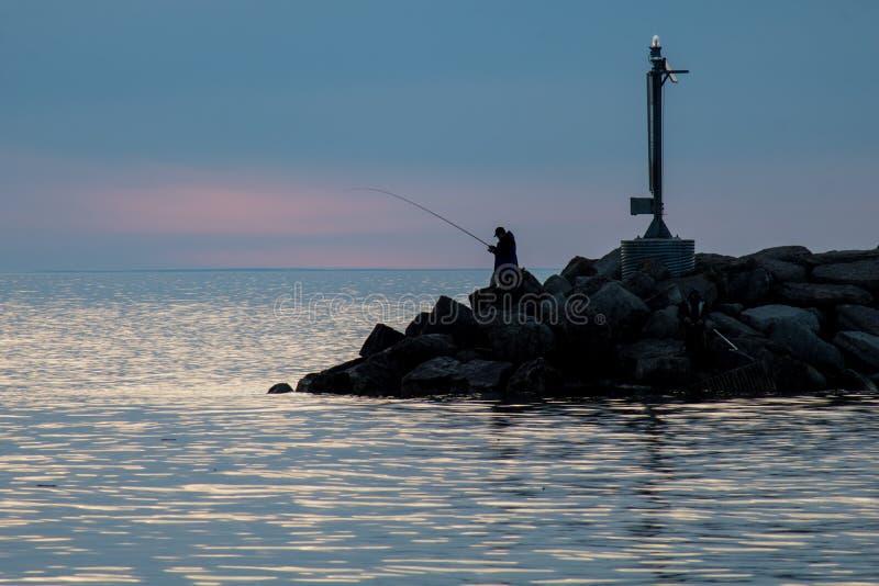 Früher Morgen-Fischer auf dem Wellenbrecher lizenzfreies stockbild