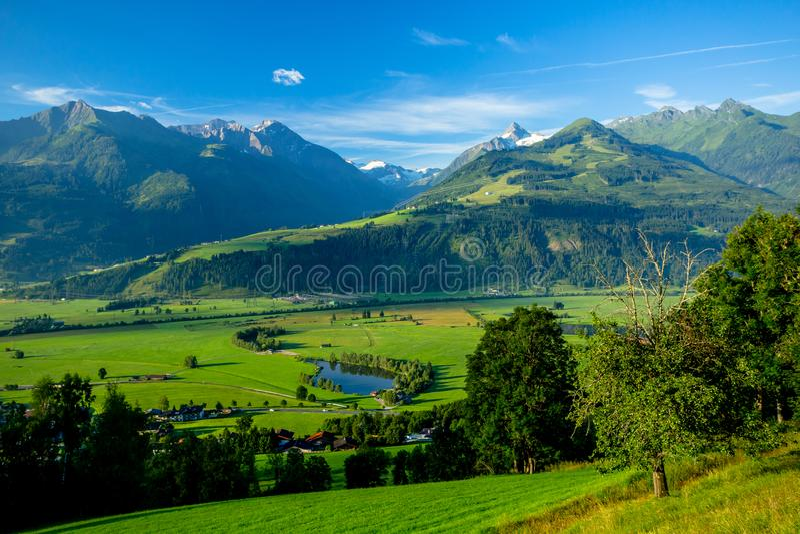 Früher Morgen-klare Sicht der Wiesen nahe Piesendorf mit dem Snowy Kitzsteinhorn im Hintergrund stockbild