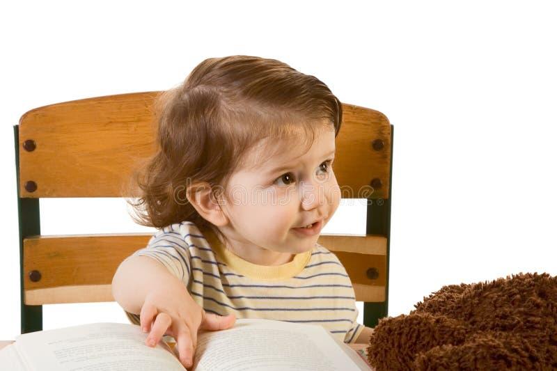 Frühes Ausbildungs-Baby mit Buch am Schuleschreibtisch stockfoto