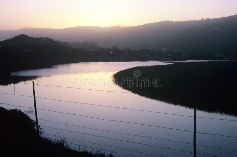 Frühes Morning gebogener See mit Zaun lizenzfreie stockfotografie