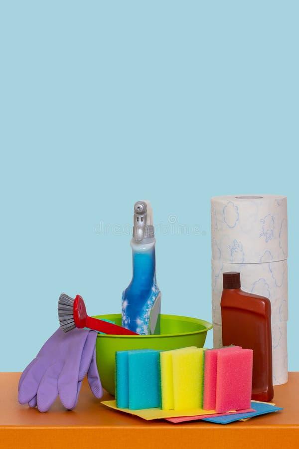 Frühjahrsputzhintergrund Nahaufnahme von Hausreinigungsprodukten und -Putzzeug auf Holztisch über hellblauem Hintergrund lizenzfreie stockfotos
