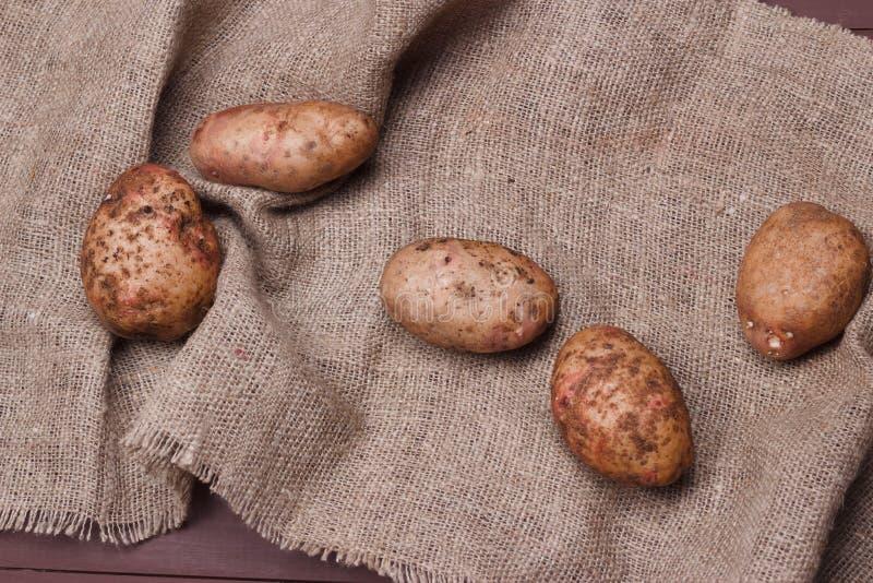 Frühkartoffeln auf Sackleinen auf Holztisch, Draufsicht stockfoto
