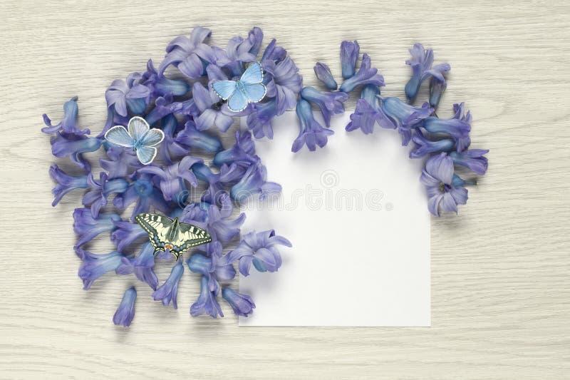 Frühling blüht mit Schmetterlingen und leerem Papierblatt auf weißer rustikaler Tabelle lizenzfreie stockfotografie