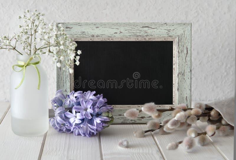 Frühling blüht um eine Tafel im rustikalen Rahmen, Textraum lizenzfreies stockfoto