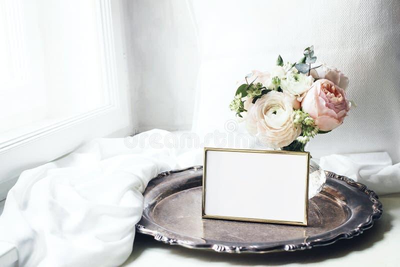 Frühling, Sommerstillleben Leeres goldenes Fotorahmenmodell auf altem Silbertablett nahe Fenster Weibliches angeredetes Foto der  lizenzfreie stockfotografie
