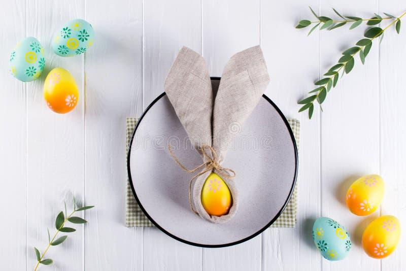 Frühlings-festliches Ostern-Gedeck mit Häschenohr-Leinenserviette und Küchentischbesteck Flache Lage stockfoto