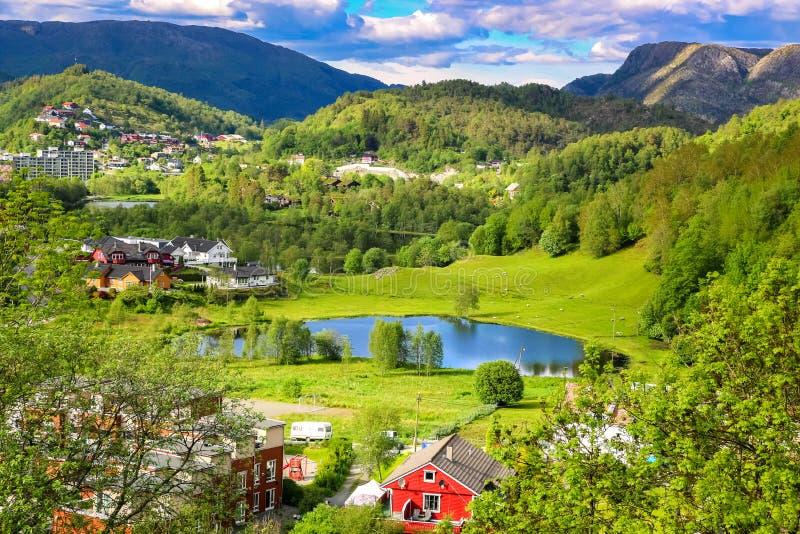 Frühlings-Landschaft mit Überblick über ein ruhiges Tal mit grünen Wiesen, einem Teich und bunten Gutshäusern im Sonnenlicht stockfotos