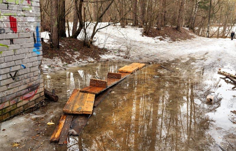 Frühlings-Tauwetter Holzbrücke über einer Pfütze im Stadtpark Balashikha, Russland lizenzfreie stockfotografie
