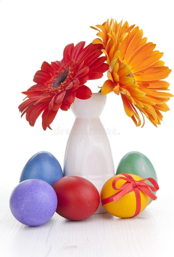Frühlingsblumen im Vase mit Ostereiern lizenzfreie stockfotos