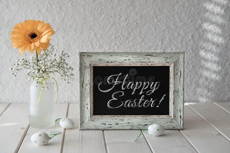 Frühlingsblumen, Ostern-Dekorationen und eine Tafel auf weißem Vorsprung lizenzfreies stockbild