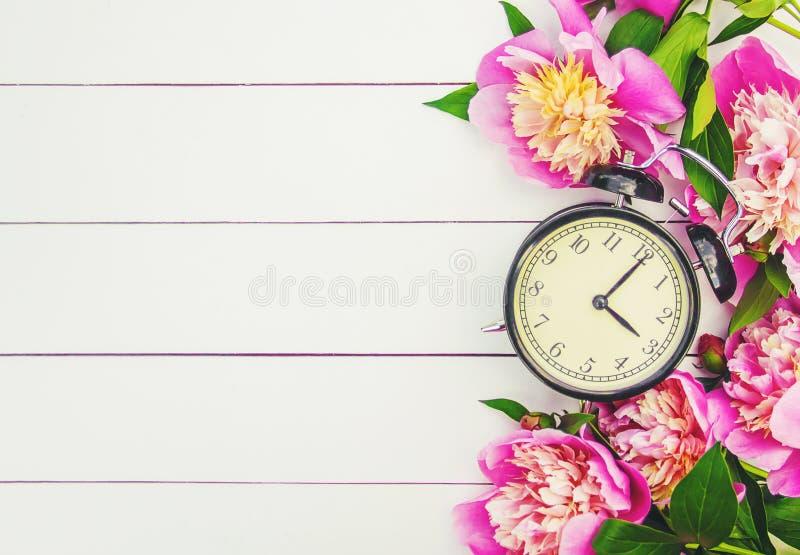 Frühlingsblumen und -Wecker Ändern Sie die Zeit stockbilder
