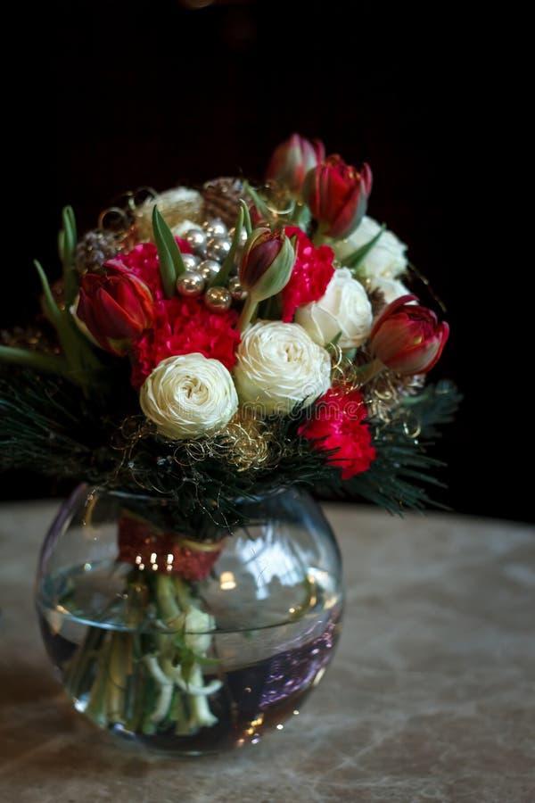 Frühlingsblumenstrauß des weißen Ranunculus und der roten Tulpen in einem runden GlasVase auf einem dunklen Hintergrund lizenzfreie stockfotos
