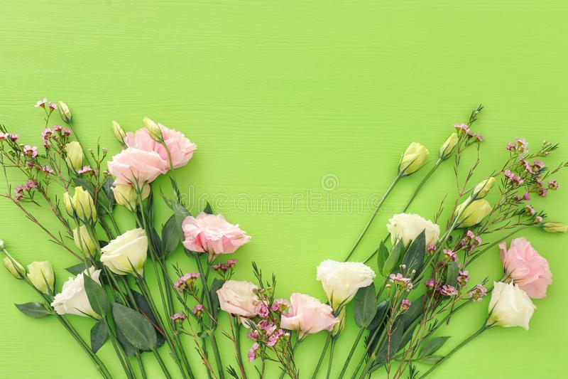 Frühlingsblumenstrauß von Pastell- und empfindlichen rosa Blumen über grünem hölzernem Hintergrund Draufsicht, flache Lage lizenzfreie stockbilder