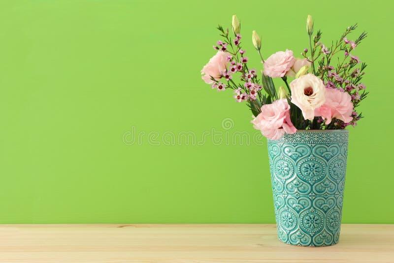 Frühlingsblumenstrauß von Pastell- und empfindlichen rosa Blumen im Vase über Holztisch lizenzfreies stockbild