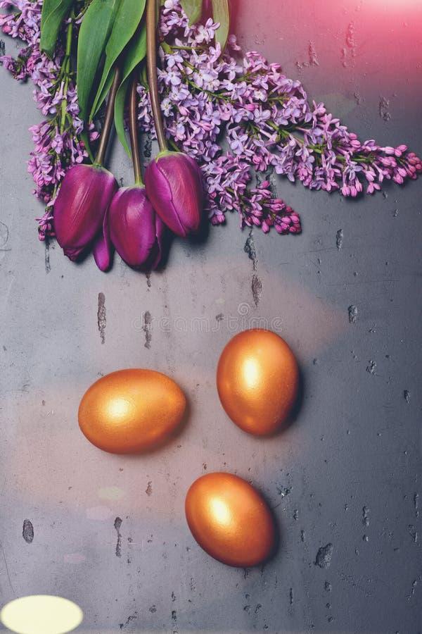 Frühlingsblumenstrauß von Tulpen und von lila nahen goldenen Eiern lizenzfreies stockbild