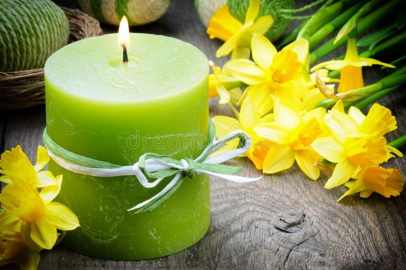 Frühlingseinstellung mit gelber Narzisse und Kerze stockfoto