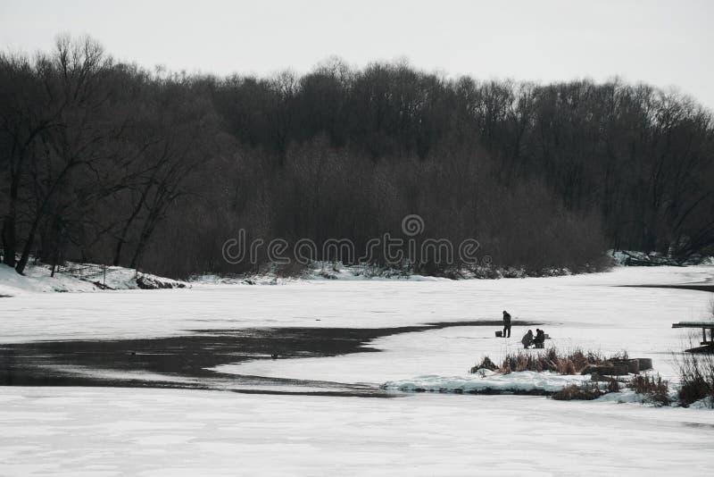 Frühlingsfluß fängt an zu schmelzen und Fischer auf dem Eis lizenzfreie stockfotos