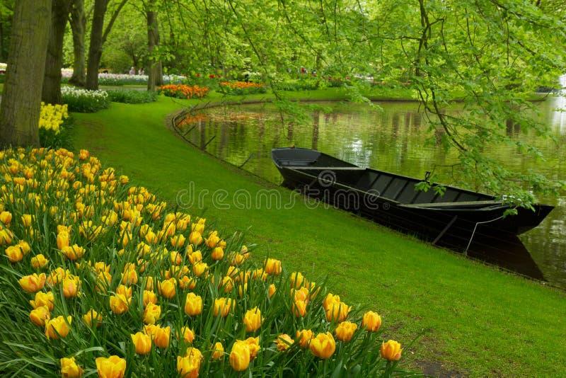 Frühlingsgarten mit Kanal und Boot lizenzfreie stockfotos