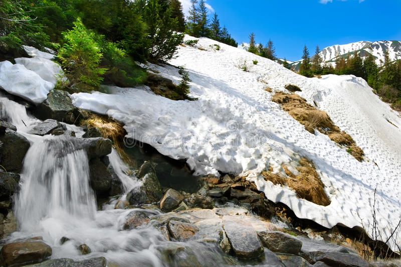 Frühlingsgebirgslandschaft mit Schnee und Wasserfall stockbilder