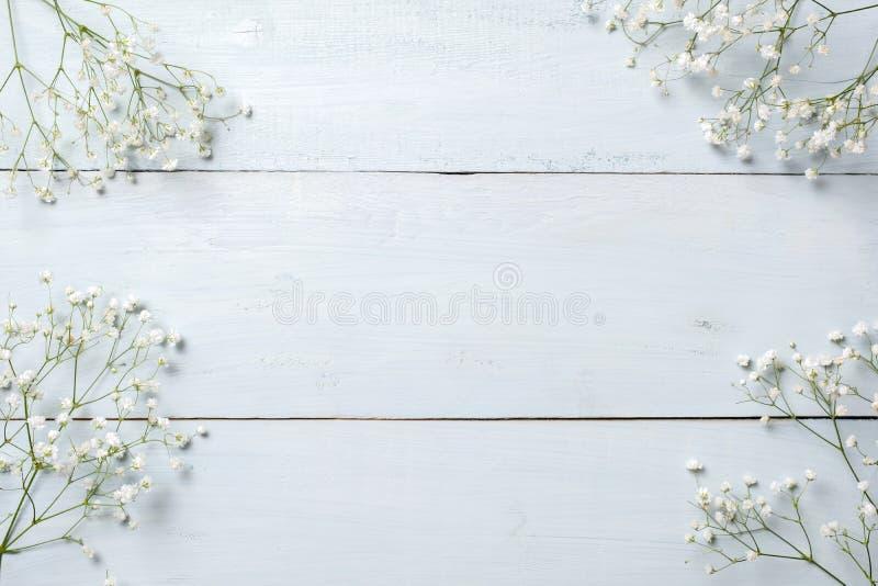 Frühlingshintergrund, Blumenrahmen auf blauem Holztisch Fahnenmodell für den Tag der Frau oder Mutter-, Ostern, Frühlingsfeiertag stockfoto