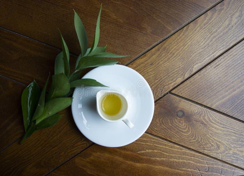 Frühlingshonig mit einer weißen Tasse auf einer Untertasse lizenzfreies stockbild