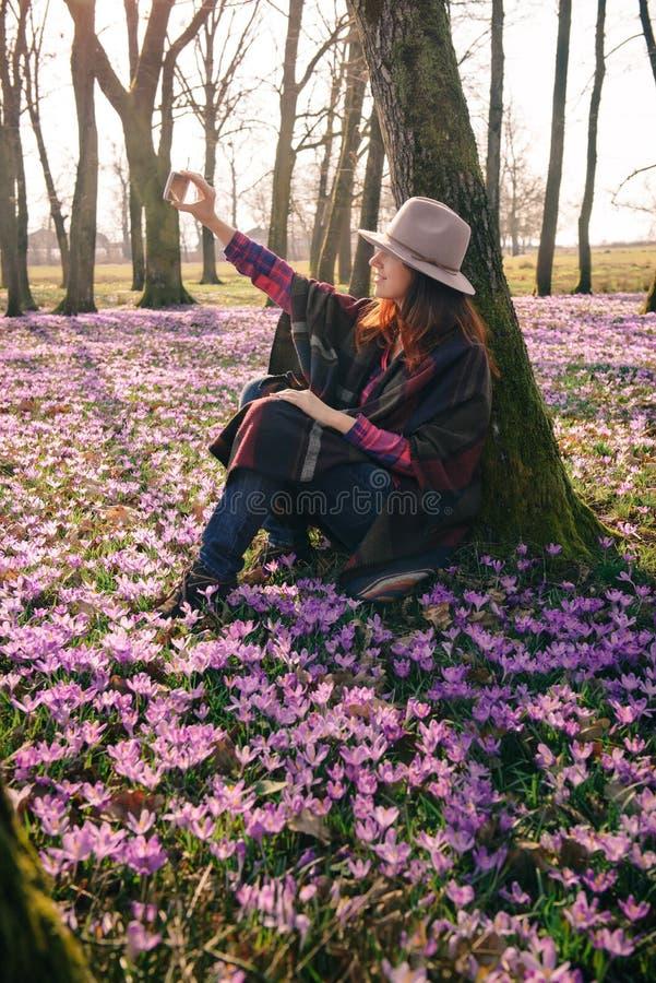 Frühlingskrokusse im Wald und in einem weiblichen Reisenden stockfoto
