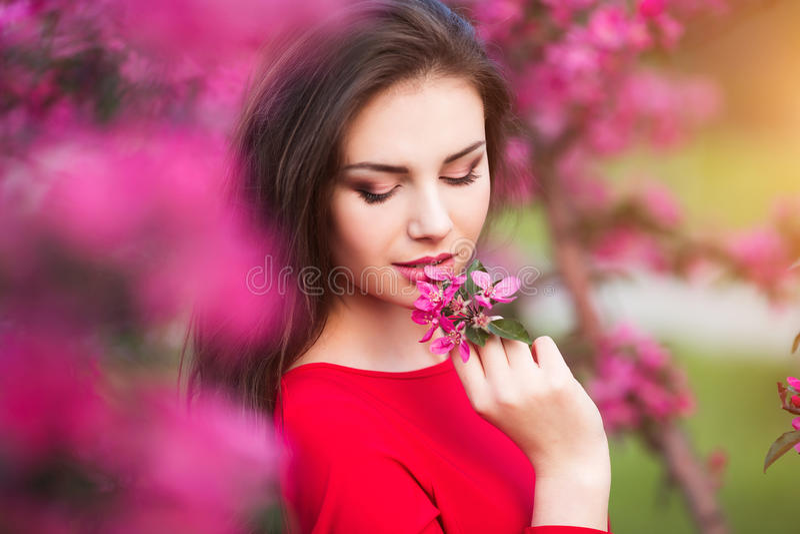 Frühlingsnote Glückliche schöne junge Frau im roten Kleid genießen neue rosa Blumen und Sonnenlicht im Blütenpark bei Sonnenunter stockbilder