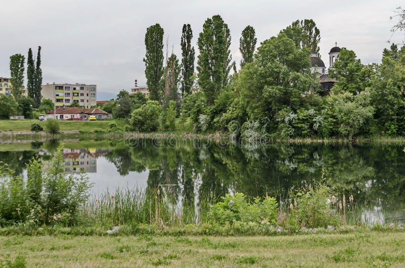 Frühlingspanorama eines Teils der Wohnviertelnachbarschaft entlang einem See mit grünen Bäumen, Sträuchen und Blumen stockbilder