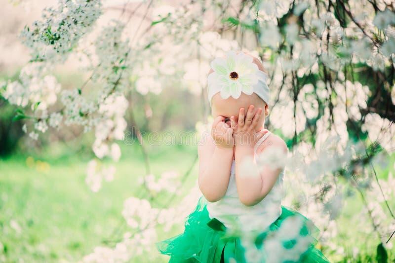 Frühlingsporträt des netten Babys im grünen Rock im Freien in blühendem Garten genießend Weg stockfoto