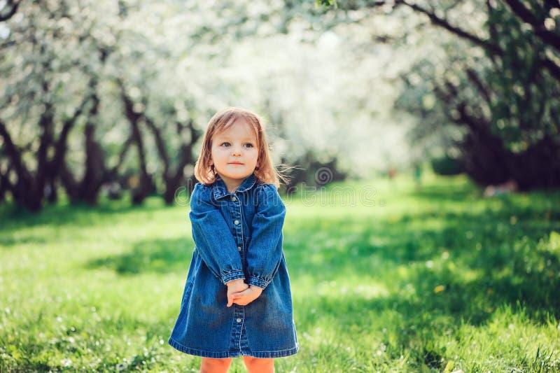 Frühlingsporträt des netten kleinen Kleinkindmädchens in den Blue Jeans kleiden das Gehen in blühenden Park lizenzfreie stockbilder
