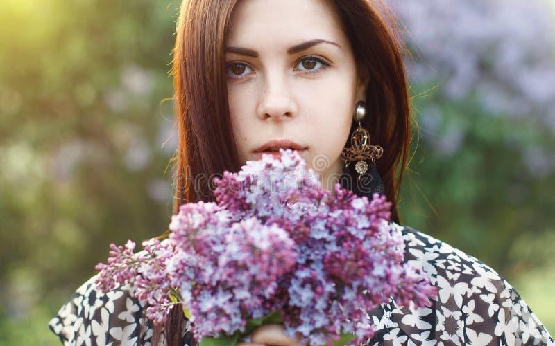 Frühlingsporträt einer hübschen Frau, die eine Flieder hält, blüht outdo lizenzfreie stockfotografie