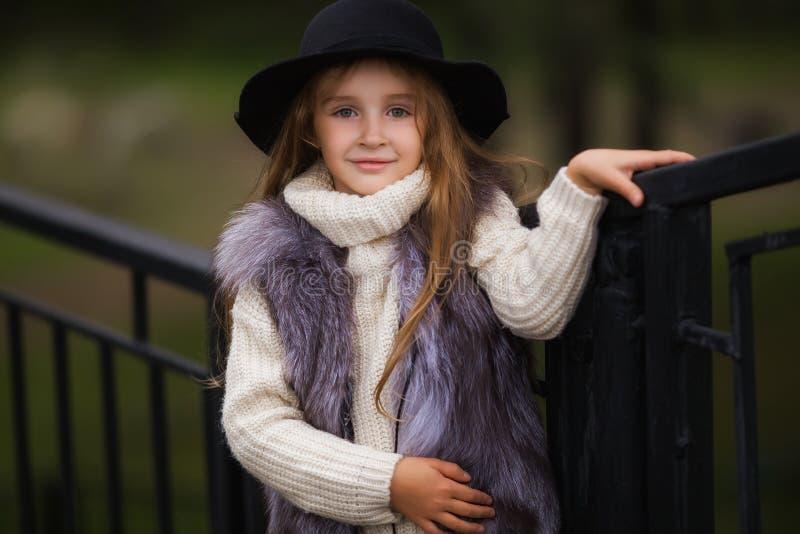 Frühlingsporträt eines kleinen Mädchens Süßes Mädchen mit großen braunen Augen in einem schwarzen Hut und ein Pelz bekleiden stockfoto