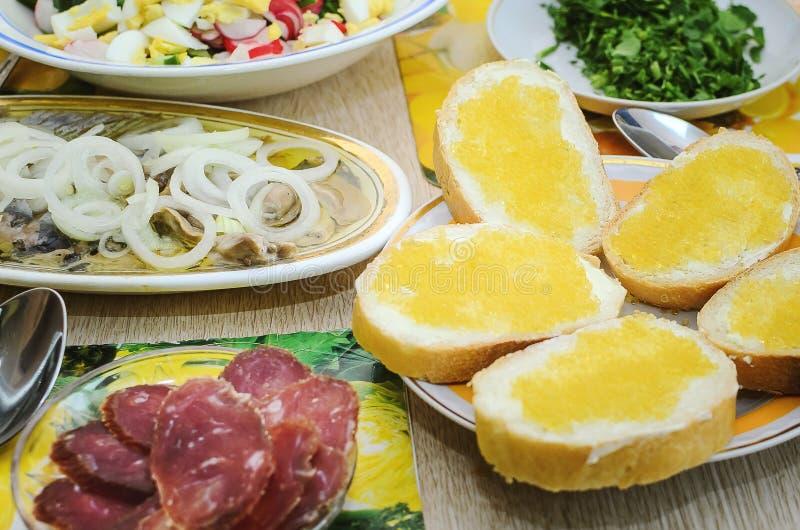 Frühlingssalat mit Eiern, Gurken und Rettiche, Heringe mit Zwiebeln und gehackter Wurststand auf dem Tisch Nützliches und geschma stockfoto