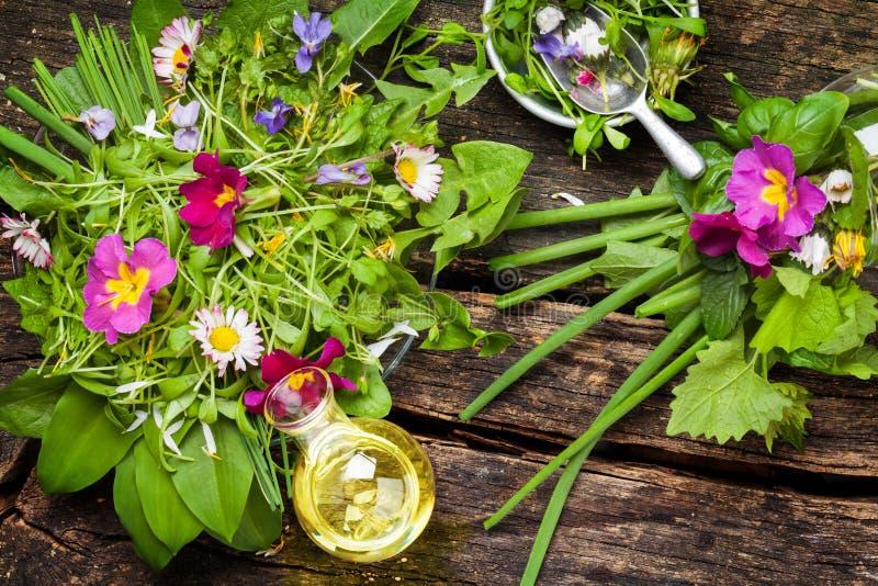 Frühlingssalat - wilde Kräuter, essbare Blumen und Öl stockfotos
