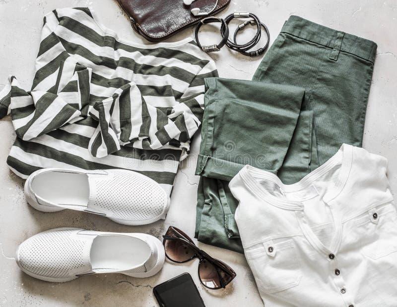 Frühlingssommersatz Freizeitkleidung der Frauen - Baumwollhose, weißes T-Shirt, gestreifter Pullover, lederne Turnschuhe, Tasche, lizenzfreies stockbild