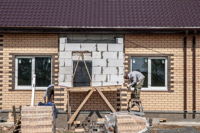 Frühlingstag, Arbeitskräfte machen die Endfassade vom Haus lizenzfreie stockbilder