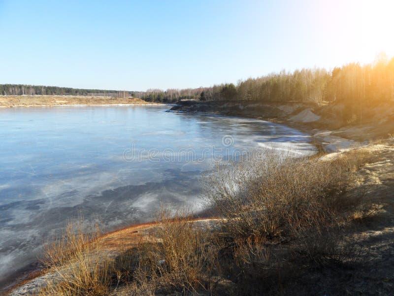 Frühlingsufer der Bucht im Wald mit Überresten von schmelzenden Eisschollen am sonnigen Tag lizenzfreie stockbilder