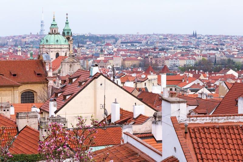 Frühlingsvogelperspektive auf Häusern und alten roten Dächern der alten Stadtstadt Prags einschließlich St. Nicholas Church Tsche lizenzfreie stockfotos