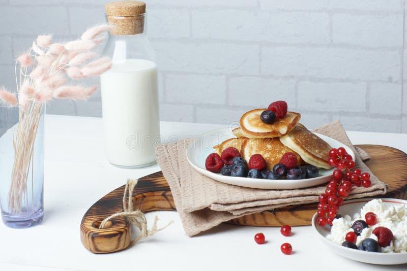 Frühstück auf einer weißen Tabelle, Pfannkuchen mit Beeren, frischem Hüttenkäse und einer Flasche Milch lizenzfreie stockbilder