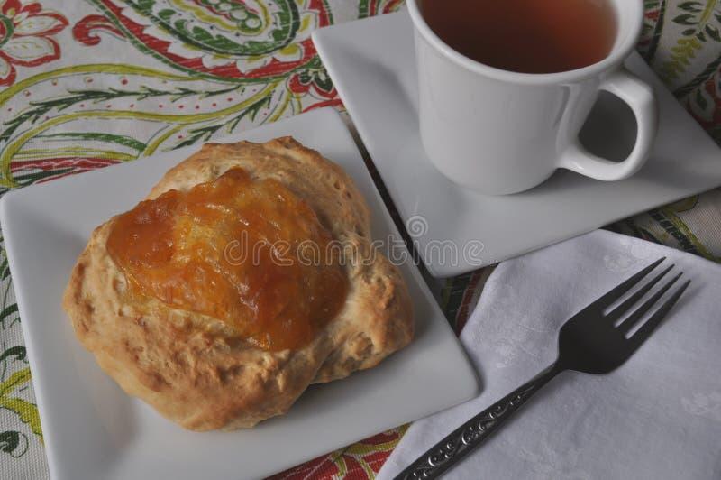 Frühstück der einzelnen Person des süßen Gebäcks mit Fruchtmarmelade und einer Schale heißem Tee auf einem bunten Hintergrund lizenzfreies stockfoto