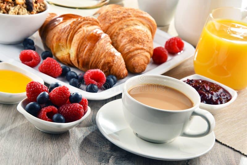 Frühstück diente mit Kaffee, Saft, Hörnchen und Früchten stockfotografie