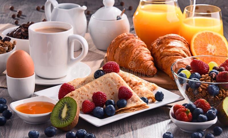 Frühstück diente mit Kaffee, Saft, Hörnchen und Früchten stockbild