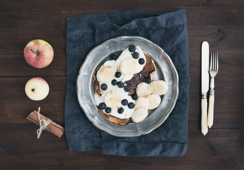 Frühstück eingestellt auf dunklen hölzernen Schreibtisch: Apfel- und Zimtpfannkuchen lizenzfreie stockfotos
