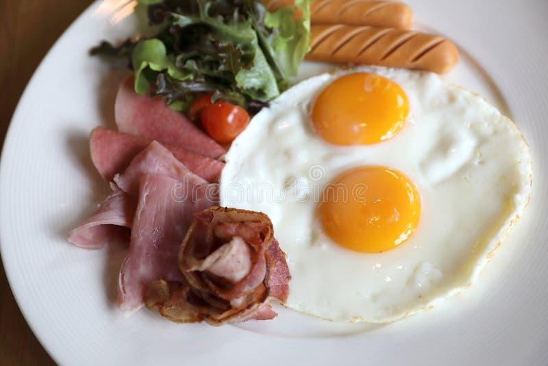 Frühstück eingestellt mit Spiegeleiern, Speck, Würsten, Bohnen, Toast, frischem Salat und Frucht auf hölzernem tabl lizenzfreie stockfotos