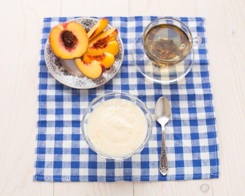 Frühstück. Grüner Tee, youghurt und Pfirsich stockfoto
