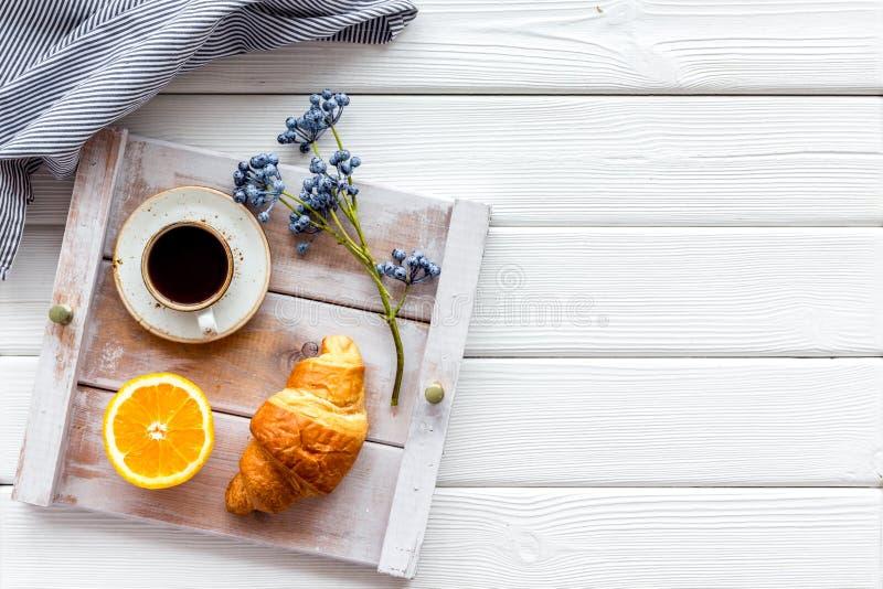 Frühstück im Bett mit Hörnchen, Kaffee in der Schale mit Orange auf Behälter auf Draufsicht des weißen hölzernen Hintergrundes lizenzfreies stockbild