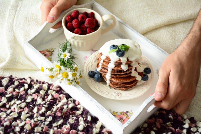 Frühstück im Bett: Schokoladenpfannkuchen mit Jogurtsoße und -beeren stockfotografie