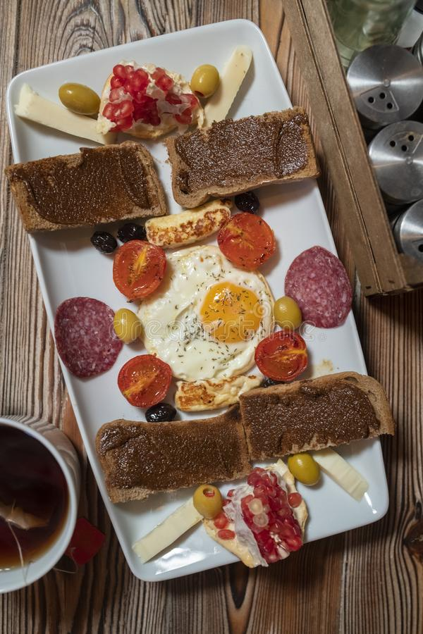 Frühstück mit Spiegelei, Roggenbrot, Granatapfel, Johannisbrotbaumpaste, Käsen, Oliven, trockener Salami, Tomaten und Tee lizenzfreies stockbild