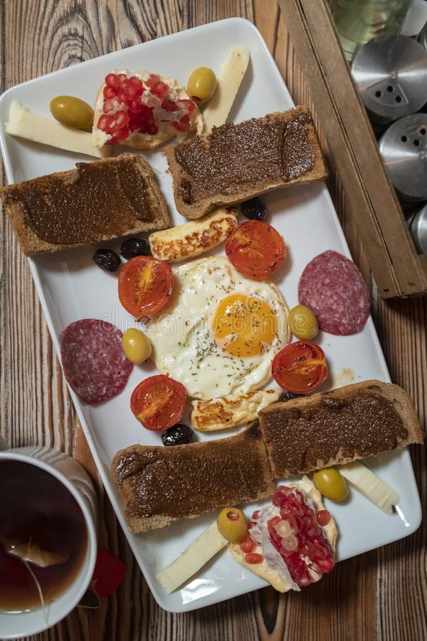 Frühstück mit Spiegelei, Roggenbrot, Granatapfel, Johannisbrotbaumpaste, Käsen, Oliven, trockener Salami, Tomaten und Tee lizenzfreie stockfotos