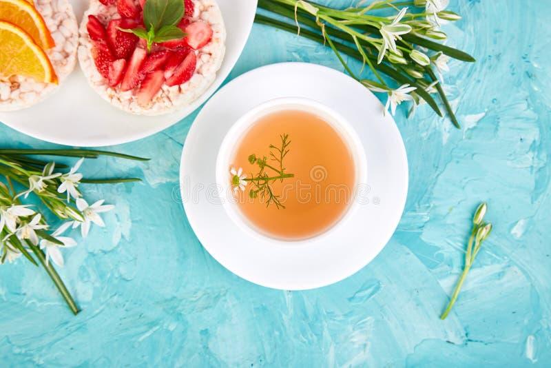 Frühstück - Tee, Reisknuspriges brot mit frischen Früchten auf blauem Hintergrund stockbilder